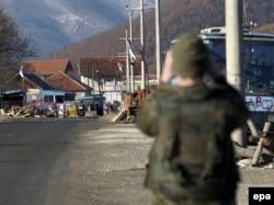 Vojnik KFOR-a posmatra barikadu u selu Zupče, 9. decembar 2011.