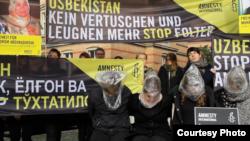 Amnesty International уюму кыйноолорду токтотуу талабы менен Өзбекстандын Берлиндеги элчиканасынын жанында уюштурган акция. 2014-жыл, октябрь.
