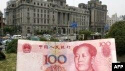 Купюра в сто юаней на фоне здания банка в Шанхае. 21 мая 2007 года.