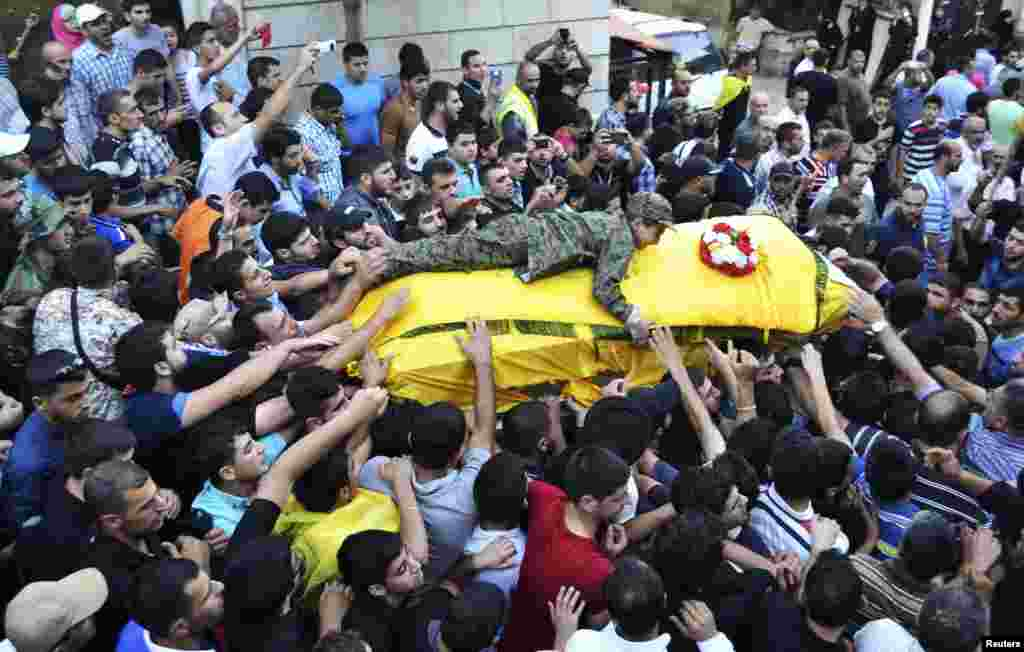 The son of Ibrahim al-Haj, a Hezbollah commander who died during a mission in Iraq, wears a military outfit as he lies on his father's coffin during his funeral in Mashghara village in the Bekaa Valley, Lebanon. (Reuters/Shawky Haj)