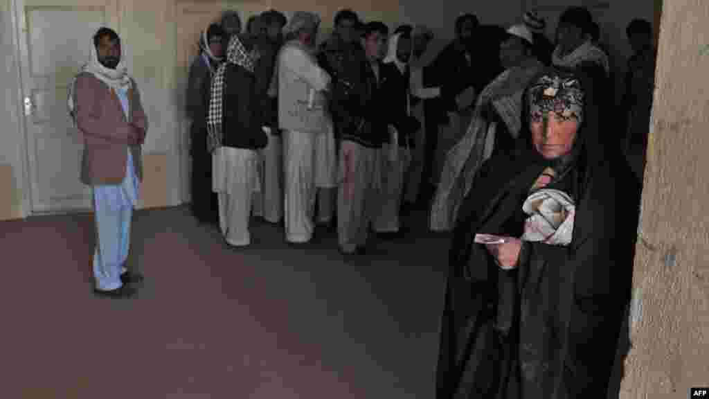 An Afghan woman who was deported from Iran to Afghanistan looks on with other returnees at the provincial refugee agency premises in Herat city in February.