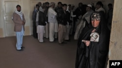 An Afghan woman who was deported from Iran to Afghanistan looks on with other returnees at the provincial refugee agency office in Herat city.