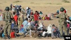 Сирийские беженцы сидят возле турецко-сирийской границы после бегства из Сирии. Турецкий город Суруч, 19 сентября 2014 года.