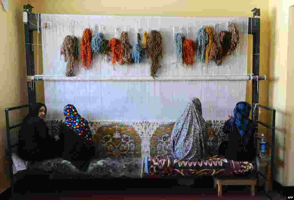 Female Afghan prisoners weave a carpet in the women's prison in Herat on August 27. (AFP/Aref Karimi)