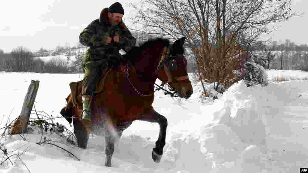 A man rides a horse through snow in the village of Vrapce, near the southern Serbian town of Medvedja, some 300 kilometers south of Belgrade.