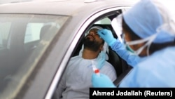 A member of medical staff takes a swab from a man during drive-through coronavirus testing at a screening center in Abu Dhabi, United Arab Emirates.