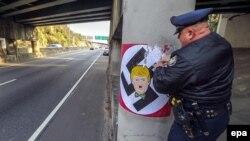 Полиция кызматкери Дональд Трампты нацисттерге окшоштурган сүрөттү сыйрып жатат. Атланта, 9-декабрь, 2015-жыл.
