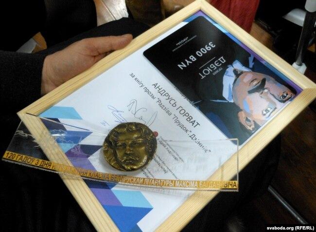 Выдавец Іван Кобзік трымае ў руках узнагароду Андруся Горвата