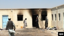Men survey a school, allegedly burned by Taliban militants, in Kandahar.