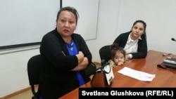 Анар Кульжанова (слева), сестра заключенного Марата Кульжанова, и его жена Инкар Жолболдиева с дочерью. Астана, 10 июля 2015 года.