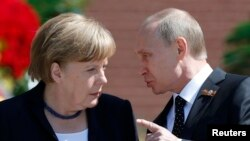 Russian President Vladimir Putin (right) speaks with German Chancellor Angela Merkel as they attend a wreath-laying ceremony at the Tomb of the Unknown Soldier by the Kremlin walls in Moscow on May 10.