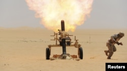 A Saudi soldier fires a mortar toward Huthi positions at the Saudi border with Yemen on April 21.