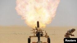 جندي سعودي يطلق قذيفة هاون في اتجاه موقع للحوثيين على الحدود بين البلدين، 21 نيسان 2015.