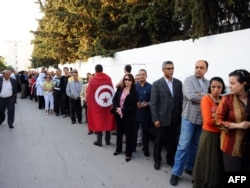 People wait in a line outside a polling station in Tunis on October 23.