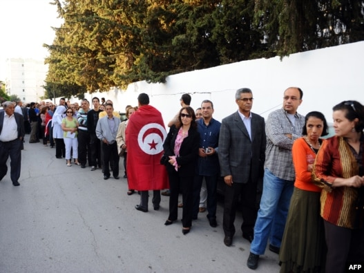 Tunisians wait in line outside a polling station in Tunis on October 23, 2011.