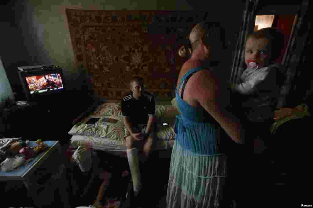 Anya Savchenko (right), Sergei Smirnov,  and their 9-month-old baby, who have fled fighting in Slovyansk, stand in their temporary accomodation in the town of Nyzhnya Krynka.