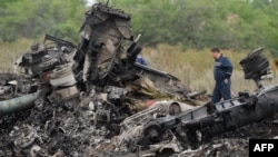 Responders stand amid aircraft parts at the crash site one day after Malaysia Airlines Flight MH17 crashed on July 19, with 298 people from 11 countries aboard, in a field near the town of Shaktarsk, in rebel-held eastern Ukraine.