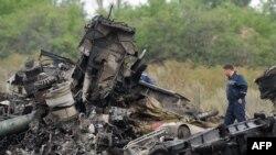 Спасатель на обломках малайзийского лайнера в Донецкой области Украины. 18 июля 2014 года.