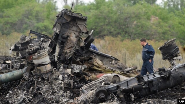 Emergency workers stand at the crash site of a Malaysian airliner, which went to ground on July 17, killing all 298 people on board.