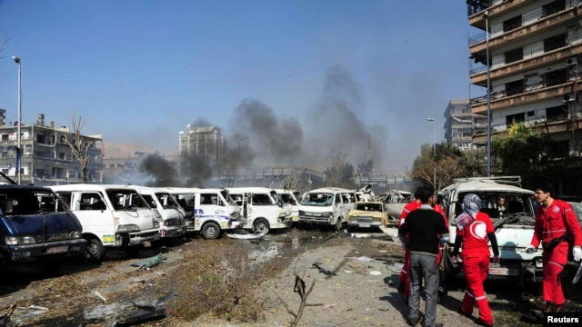 Damaged vehicles and the Russian embassy building are seen after an explosion in central Damascus on February 21.