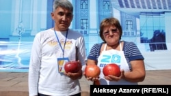 Садоводы Сапар Бекмагамбетов и Ольга Суздалева держат в руках яблоки - алматинский апорт. Алматы, 16 сентября 2012 года. Иллюстративное фото.