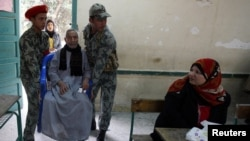 An elderly man is helped by army soldiers before casting his vote during Egypt's parliamentary elections last month.