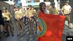 Молодая девушка, обернутая во флаг «Союза курдских студентов», стоит во время акции. Мюнхен, Германия, 9 октября 2014 года.