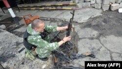 Проросійський бойовик оглядає пошкоджені автомати Калашнікова. Луганськ, 4 червня 2014 року