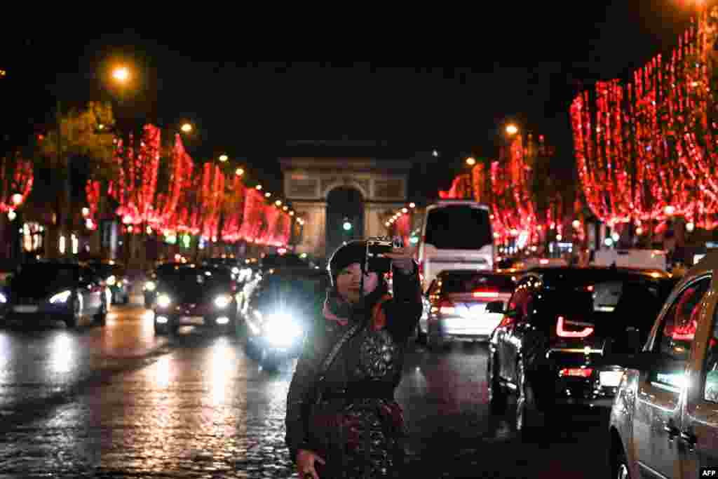 A person takes selfies on Champs Elysees avenue in Paris on November 22 after the Christmas lights were turned on. (AFP/Sergei Supinsky)