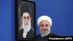 حسن روحانی در کنار عکس رهبر جمهوری اسلامی که چندی پیش بر کنار کشیدن از برجام تاکید کرد
