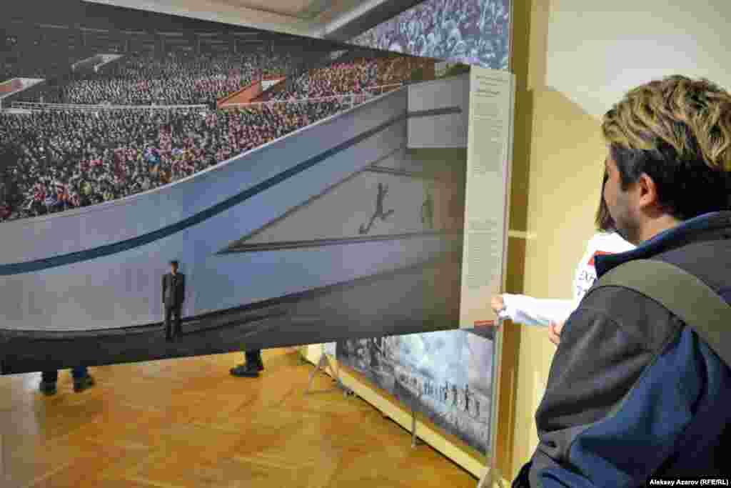 """Бұл суретті швед фототілшісі Роджер Турессон 2017 жылы 9 сәуірде әлемдегі ең жабық мемлекет - Солтүстік Кореяның астанасы Пхеньянда түсірген. Сурет """"Заман түйткілдері"""" категориясы бойынша үшінші орын алды. 50 мың адам Ким Ир Сен атындағы стадионға жиналып, марафонның басталуын күткен. Билік Роджер Турессонға түсіруге рұқсат берсе де, оның артынан арнайы қызмет өкілдері үнемі аңдып отырған. Турессон суретінің оң жақ шекесінде солардың бірін көруге болады. Ол да фотографты суретке түсіріп жатыр."""