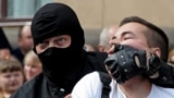 A riot police officer detains a Belarusian opposition supporter during a protest in Minsk on August 30.