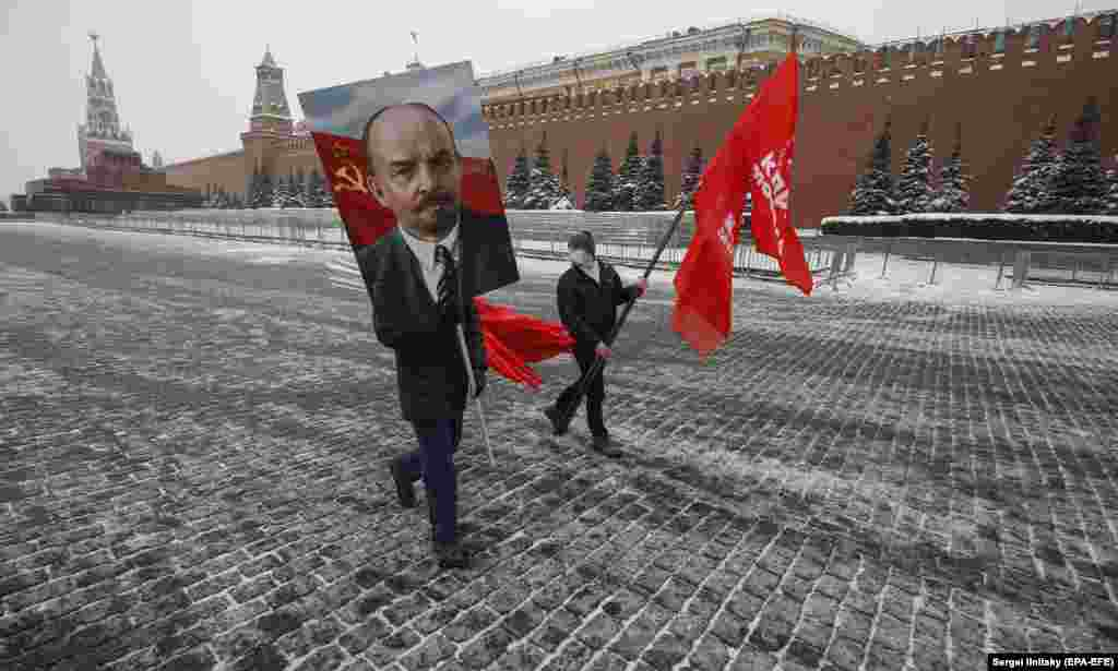 Russian communists carry a portrait of Vladimir Lenin and wave red flags to mark the 97th anniversary of the Soviet leader's death near his mausoleum in Red Square, Moscow, on January 21. (epa-EFE/Sergei Ilnitsky)