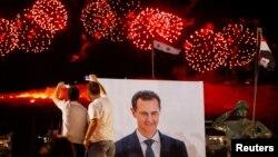 Dy burra bëjnë selfije para fotografisë së diktatorit sirian, Bashar al-Asad