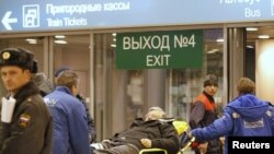 Russia -- A victim of a bomb explosion is wheeled out by medics at Moscow's Domodedovo airport, 24Jan2011