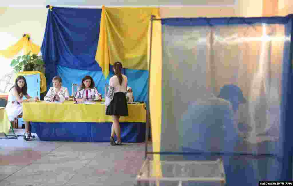 A man fills in his ballot inside a voting booth at a polling station in the village of Mshana, some 15 kilometres from the western city of Lviv.Only 424 of the 450 seats in Ukraine's parliament will be filled in these elections, as the rest represent Crimea, annexed by Russia in 2014, or territories controlled by Russia-backed separatists. (AFP/ Yuri Dyachyshyn)