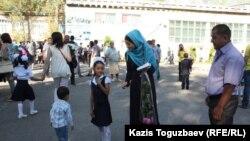 Родители с детьми-школьниками во дворе школы. Алматы, 1 сентября 2014 года. Иллюстративное фото.