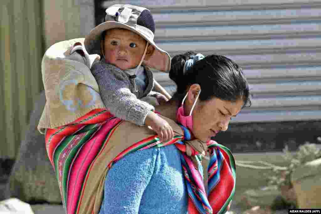 Egy őslakos nő cipeli gyermekét Bolívia nyugati részén, El Altóban 2020. május 22-én.