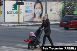 Баласын арбаға салып, көшеде келе жатқан әйел. Алматы, 13 желтоқсан 2020 жыл.