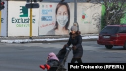 Женщина с ребенком в коляске на улице в Алматы во время пандемии. 9 декабря 2020 года.