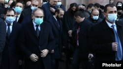 Armenian Prime Minister Nikol Pashinian (second from left) emerges from the main government building in Yerevan to lead a procession to the Erablur Military Pantheon on December 19.