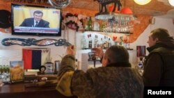 Ukrainians react as they watch a TV broadcast of ousted Ukrainian President Viktor Yanukovych's press conference on February 28.