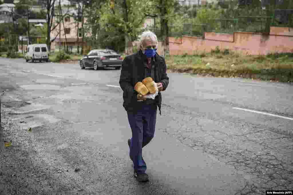 Maszkban, kenyérrel a kezében sétál haza ez a férfi. A fegyveres konfliktus mellett a koronavírussal is küzd Örményország és Azerbajdzsán.