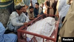 Relatives sit beside the body of a female polio vaccinator who was killed by unidentified gunman in Chaman on April 25.