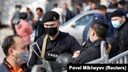 Қазақстанда Covid-19 індетін жұқтырған алғашқы науқастар анықталғаннан кейін карантинге жабылған Алматы қаласына кіреберістегі блокпостың алдындағы тұрғындар мен полицияның арнайы жасағы. Наурыз, 2020 жыл.