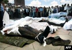 Люди смотрят на тела убитых во время стрельбы со стороны правительственных войск в Андижане. 14 мая 2005 года.
