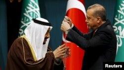 Tayyip Erdogan (sağda) Səudiyyə kralı Salmana medal verir (Arxiv)