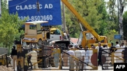 A crane removes damaged vehicles at the site of a suicide bomb attack outside the northwestern Pakistani town of Fateh Jang on June 4, 2014.