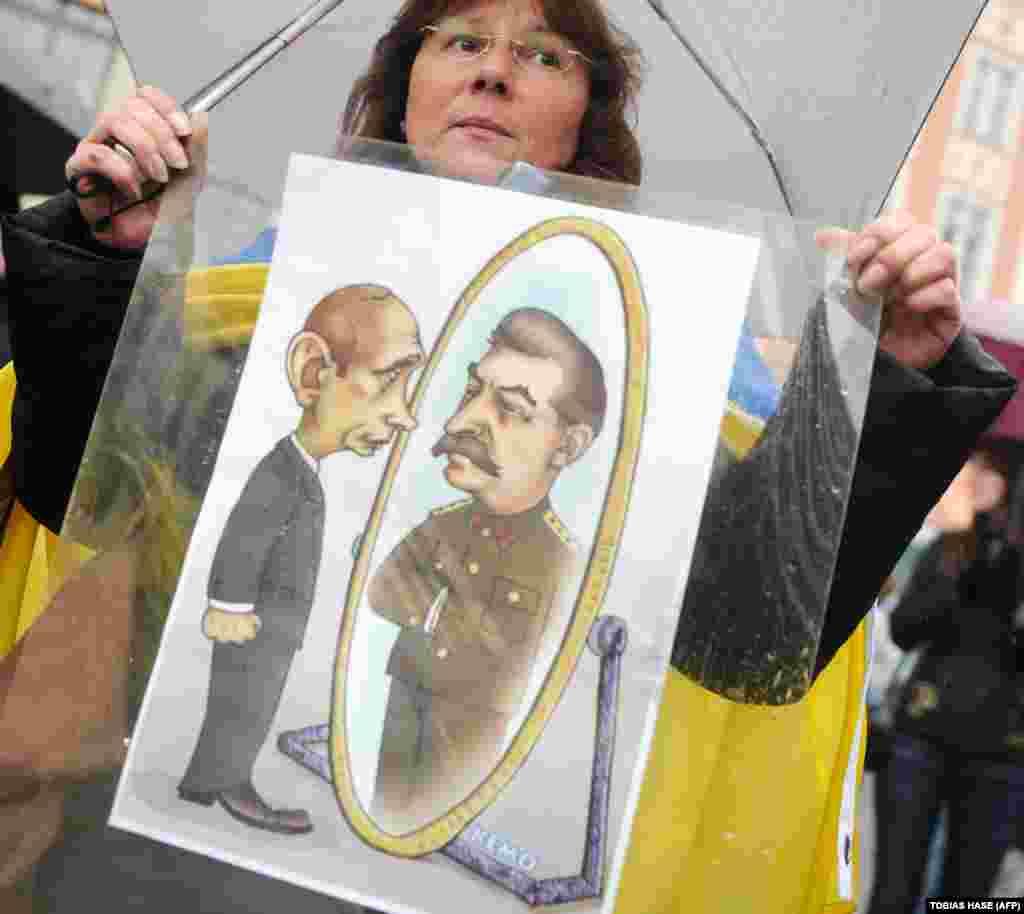 ВЕЛИКА БРИТАНИЈА / РУСИЈА / ГЕРМАНИЈА - Демонстрантка со транспарент на кој одразот на рускиот претседател Владимир Путин во огледало е поранешниот советски лидер Сталин. Велика Британија излезе со нови обвиненија дека владата на Путин стои зад труењето на поранешен шпион со нервен гас во Англија, наведувајќи дека одговорноста води до, како што беше речено, оние на врвот на руската држава.