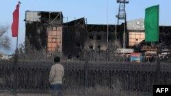 Прохожий рядом со сгоревшим зданием в Жанаозене. 18 декабря 2011 года.